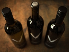 Product pictures of Van Westen Winery bottles on a vintage wooden table.